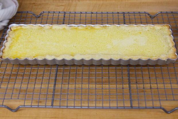 Baked lemon tart sitting on a cooling rack
