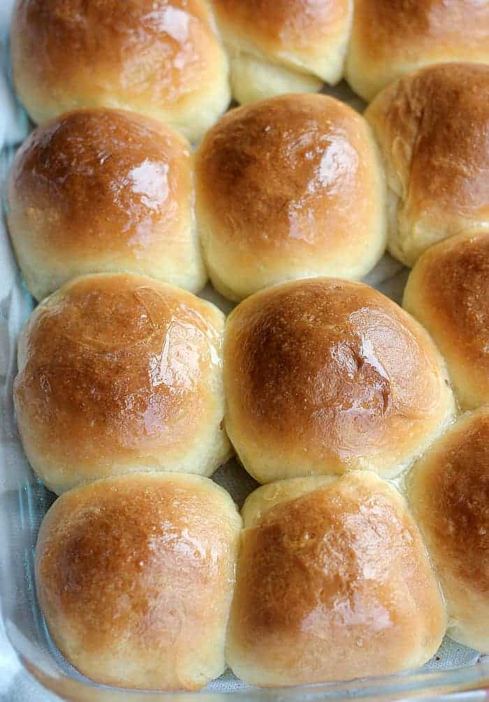 A tray of yeast rolls that have a deep golden brown and shiny appearance from the egg wash that was brushed on them