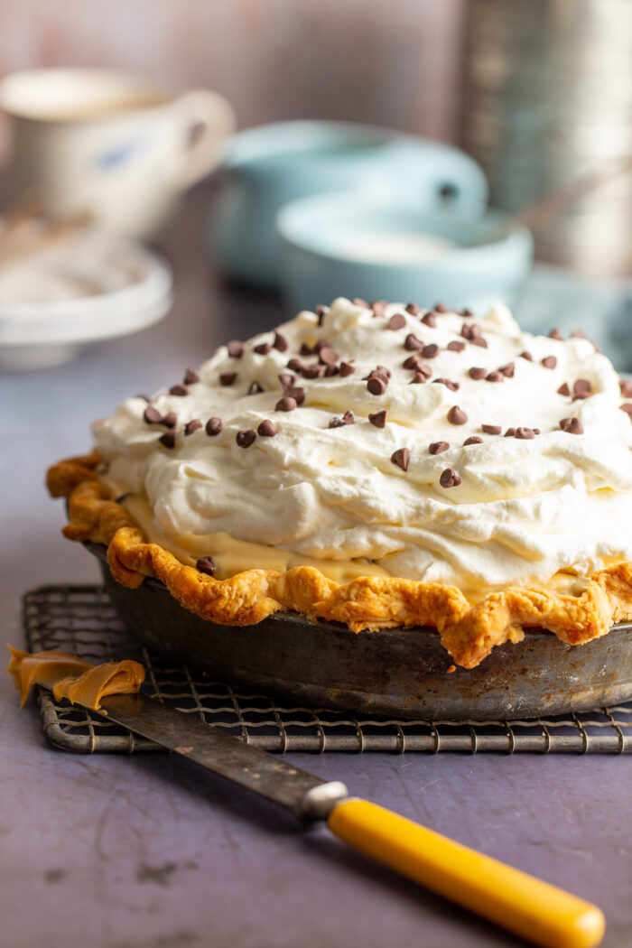 peanut butter chocolate chip cream pie in a metal tin with a knife that has some filling on it
