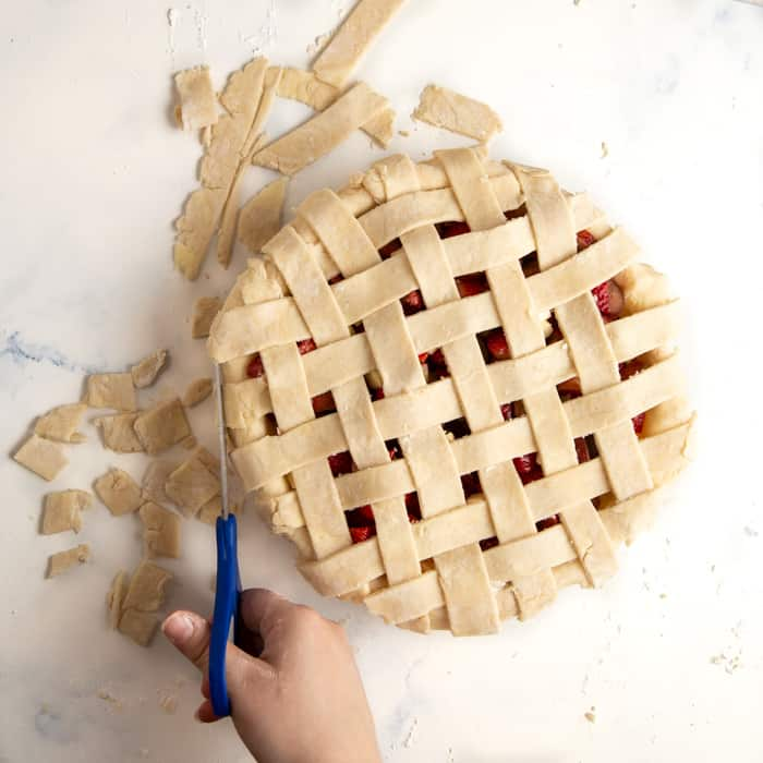 Trimming the edges of the pie dough after it has all been weaved into a lattice