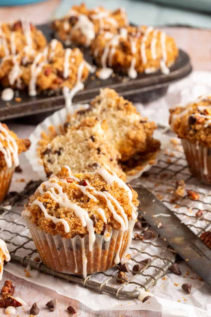 chocolate chip coffee cake muffins in muffin wrappers with vanilla glaze on top