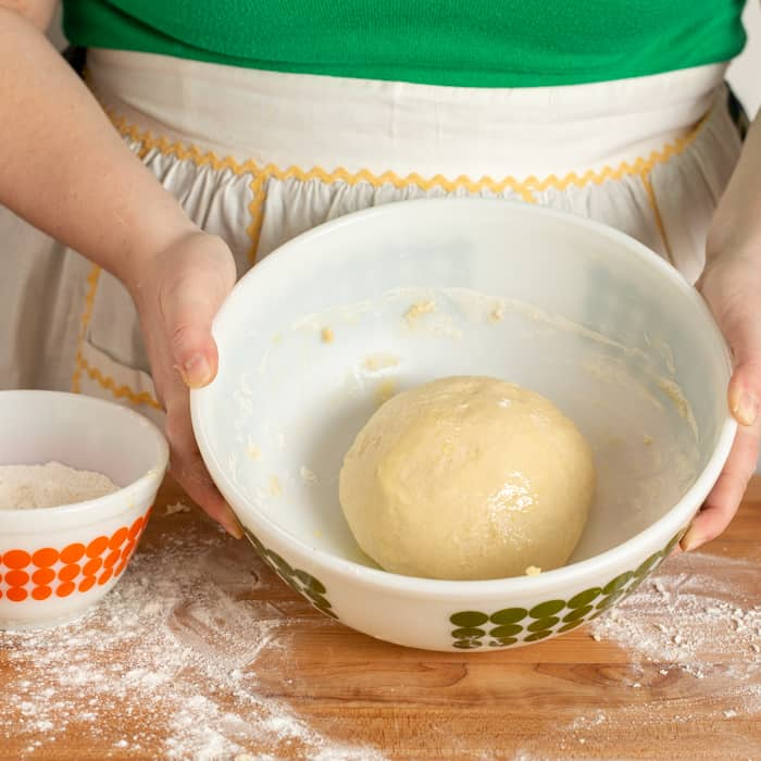 Burger bun dough in a mixing bowl coated in oil