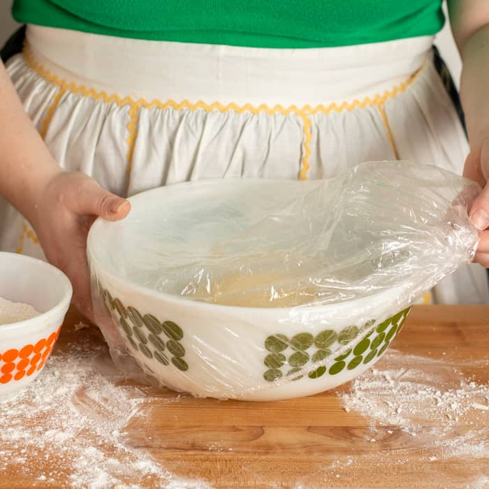 Placing shower cap over mixing bowl with dough in it