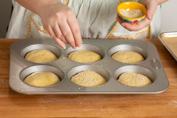 Sprinkling buns with sesame seeds