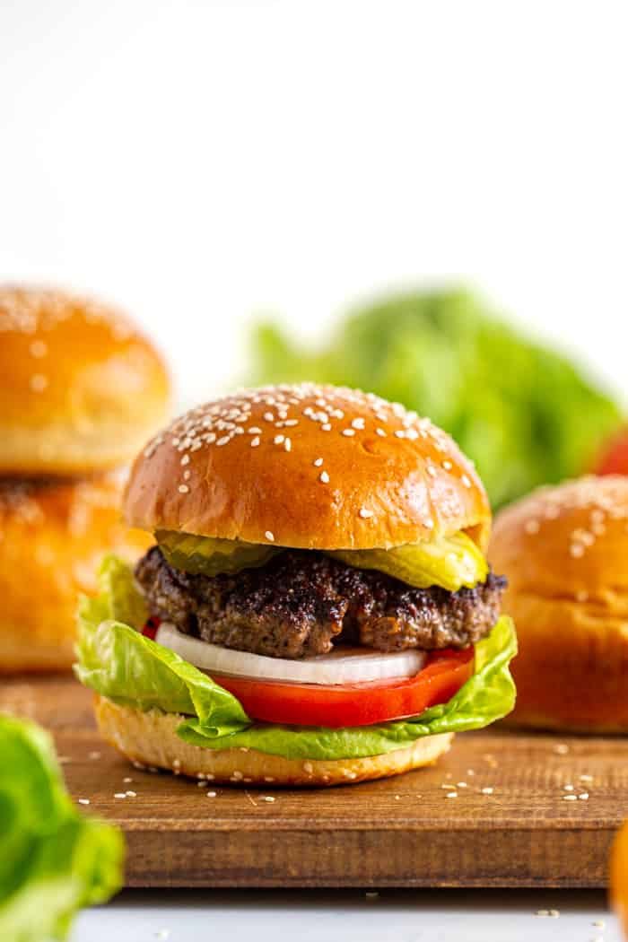 Hamburger on a homemade sesame seed bun with lettuce, tomato, onion, and pickle