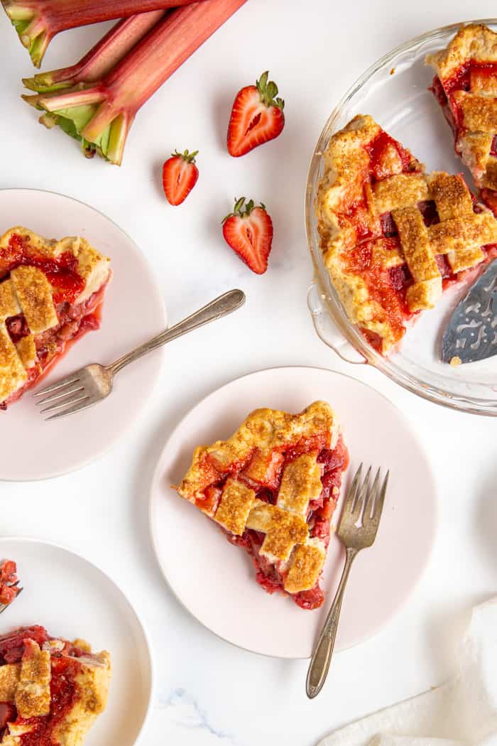 Slices of strawberry rhubarb pie on plates with fresh rhubarb and strawberries laying near