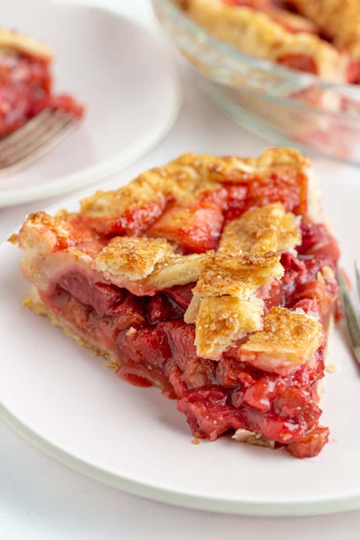 Slice of baked strawberry rhubarb pie on a plate with a lattice top crust