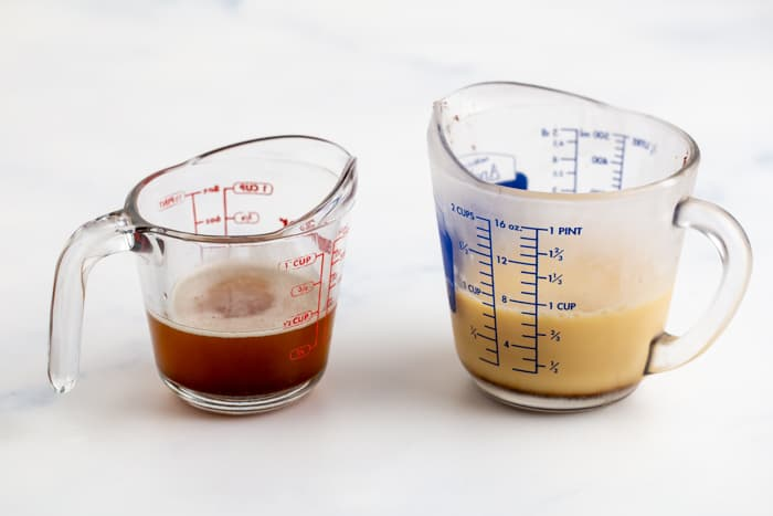 On the left is a container of liquid brown butter, on the right is a container of brown butter that has re-solidified and the milk solids have fallen to the bottom.