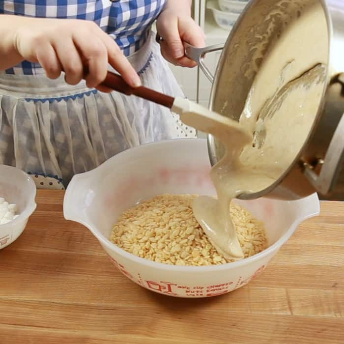 Pouring melted marshmallow/butter mixture into Rice Krispie cereal