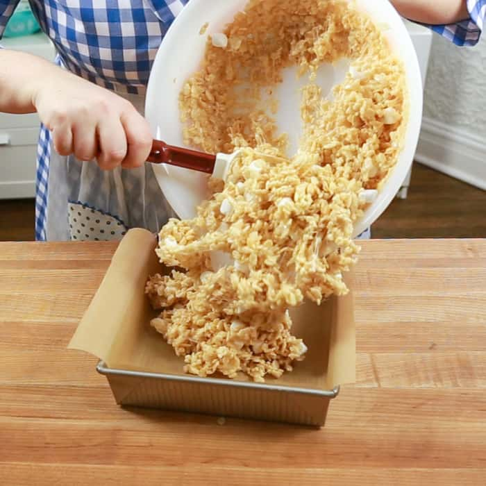 Transferring rice krispie treat mixture into parchment lined pan