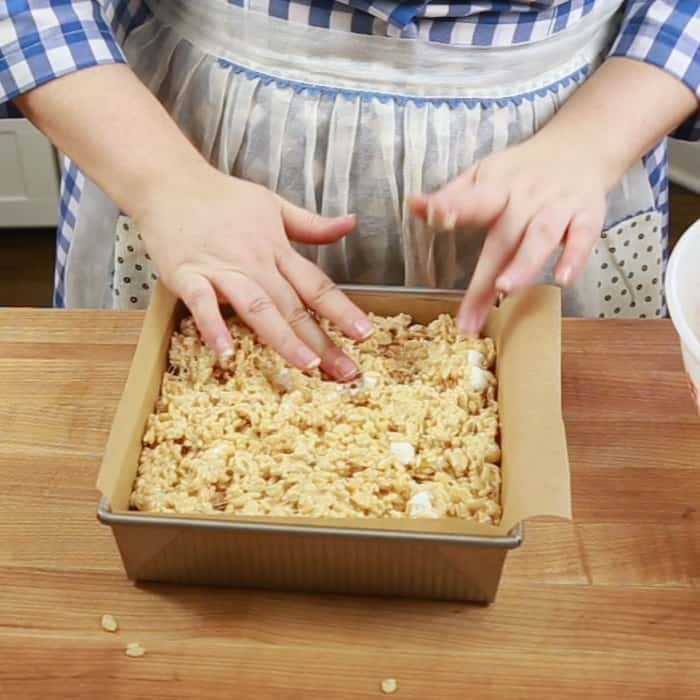 Pressing marshmallow cereal treat mixture into the pan
