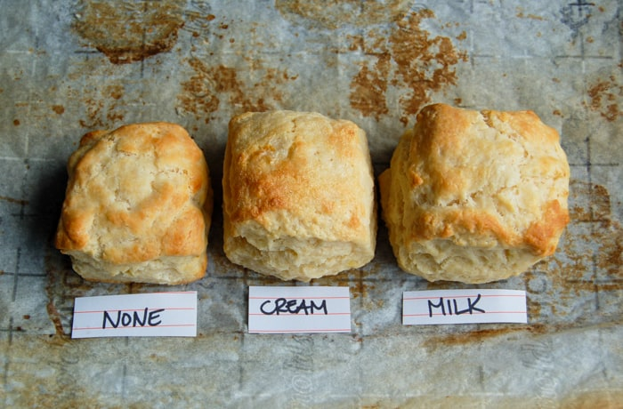 Closeup of biscuits: one brushed with nothing, one brushed with cream, one brushed with milk.
