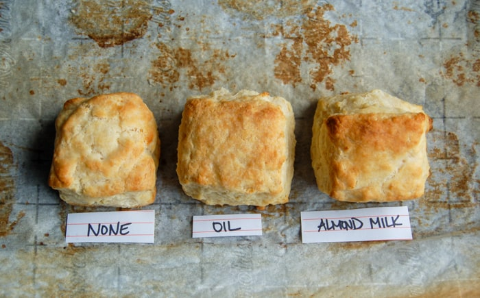 Closeup of biscuits: one brushed with nothing, one brushed with oil, one brushed with almond milk.