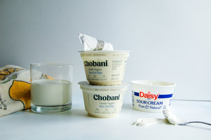 A glass of buttermilk, yogurts, and sour cream.