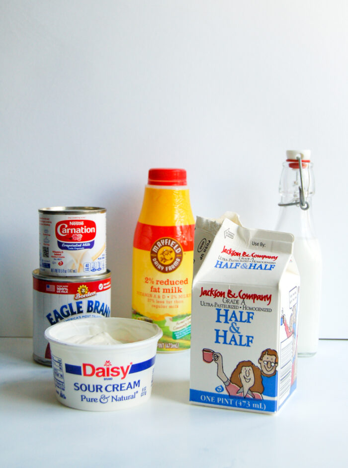 Various dairy products: carton of half and half, a container of milk, a can of evaporated milk and sweetened condensed milk, sour cream, and heavy cream.