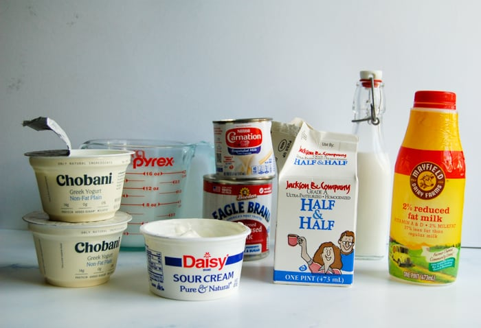 Various dairy products: carton of half and half, a container of milk, a can of evaporated milk and sweetened condensed milk, sour cream, yogurt, and heavy cream.