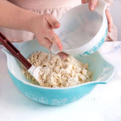 pouring water into bowl to make pie dough