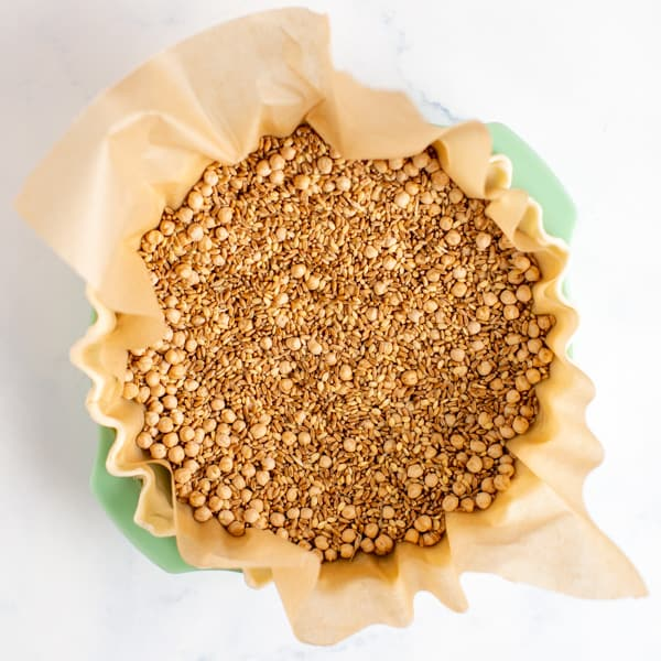 pie crust in a pie plate with parchment paper and dried beans to weigh it down