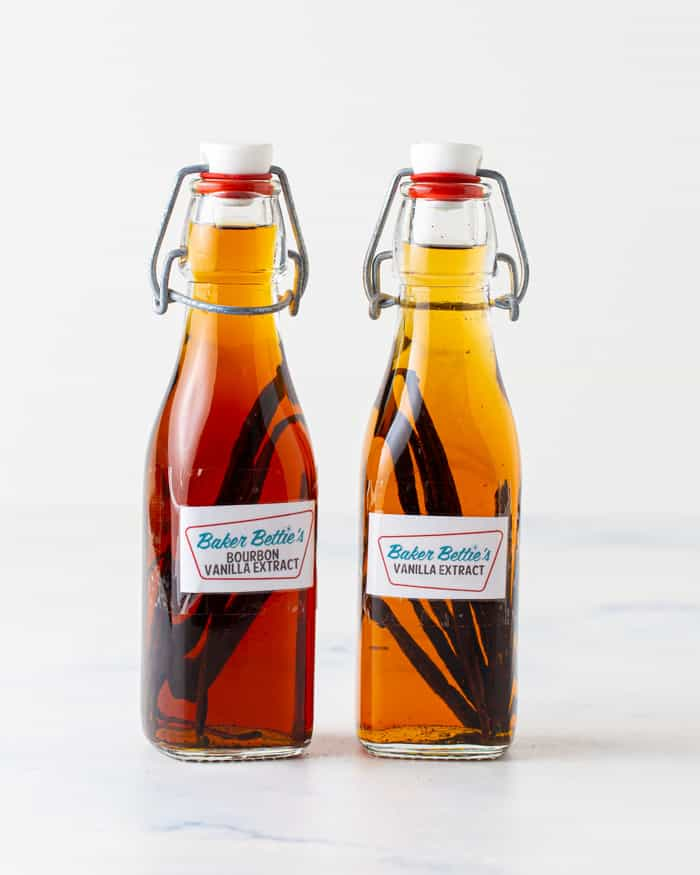 Two bottles of homemade vanilla extract sitting side by side