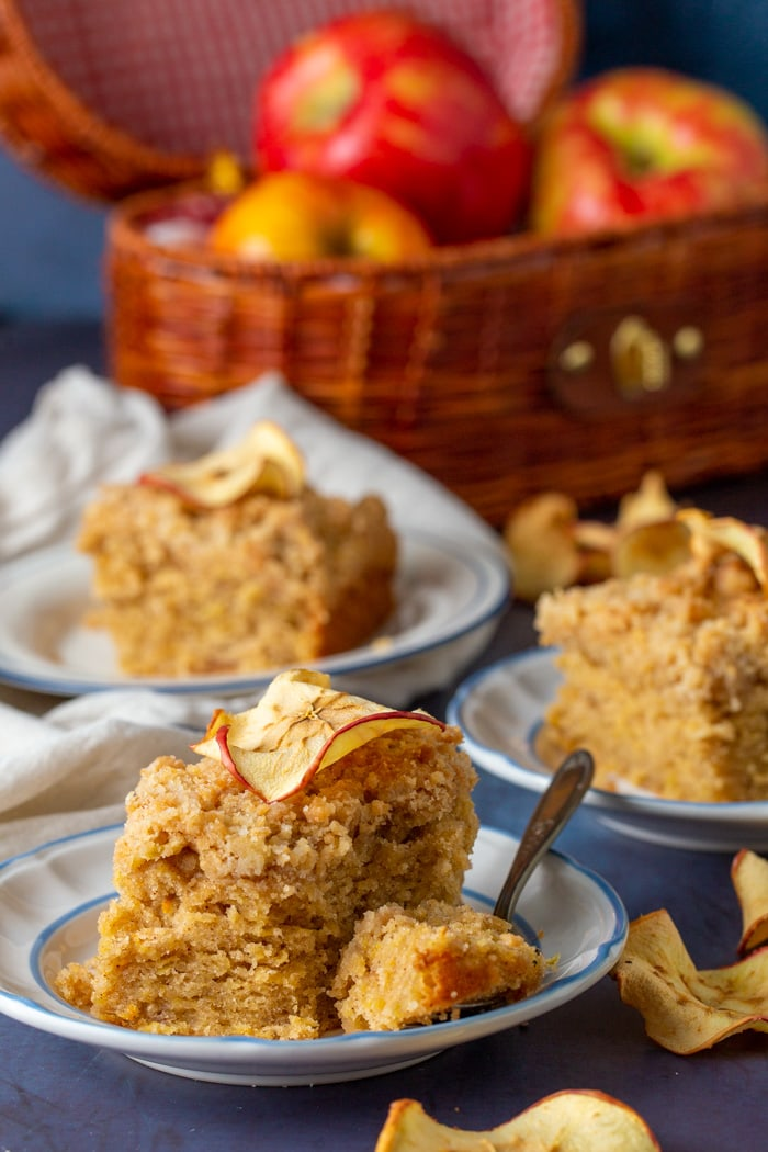 3 pieces of apple crumb cake on plates and a basket of apples