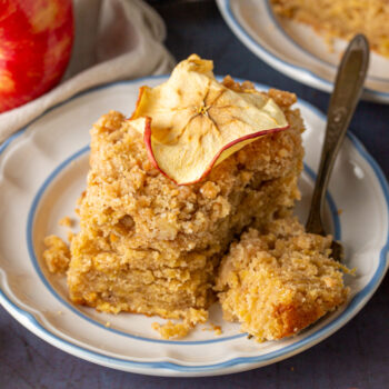 Slice of apple crumb cake on a plate with a bite on a fork and an apple chip on top