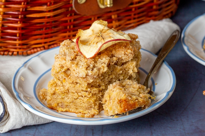 Slice of apple crumb cake on a plate with an apple crisp on top and a bite on a fork