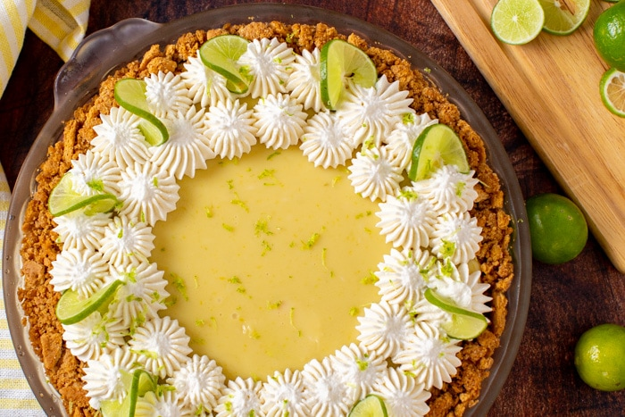 Overhead view of a classic key lime pie that is decorated with piped whipped cream and lime wedges