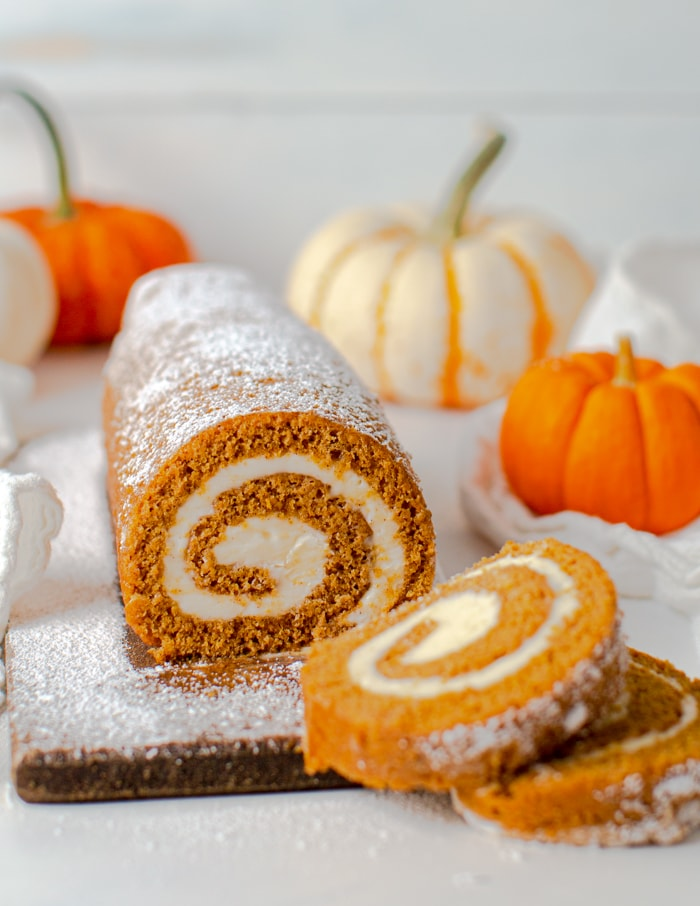cream cheese pumpkin roll on a cutting board with 2 slices cut out and pumpkins in the background