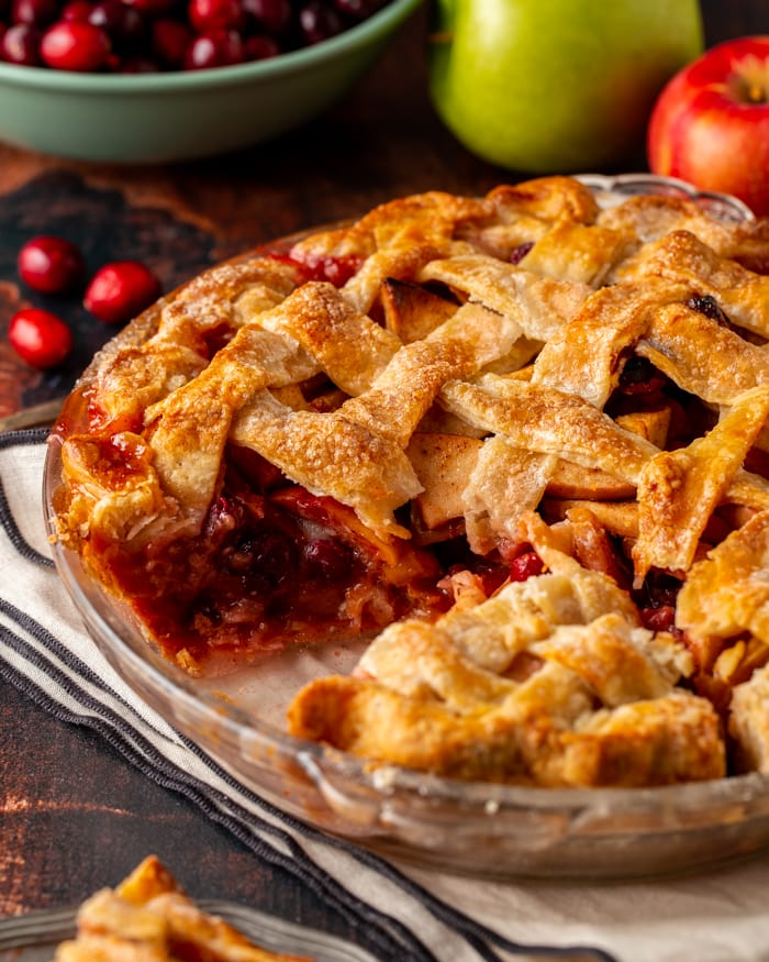Cranberry apple pie with a lattice crust and one piece cut out of it revealing the filling