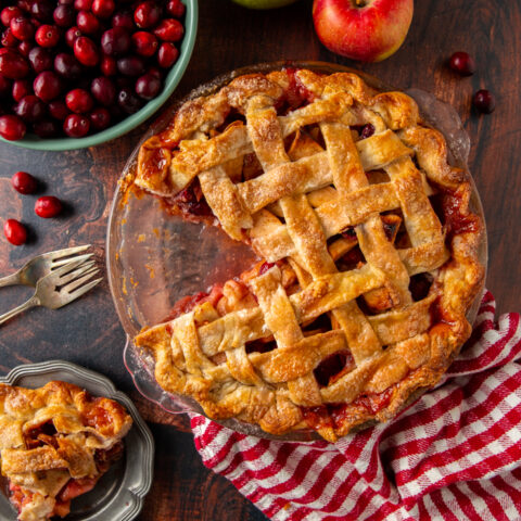 cranberry apple pie with a slice cut out of it and a bowl of cranberries
