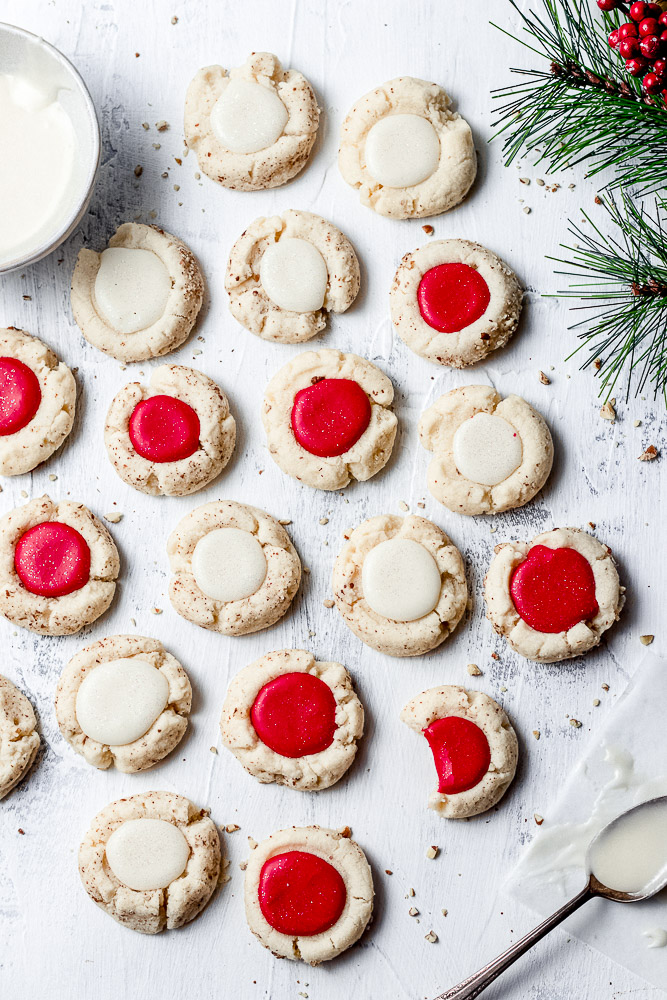 red and white pecan thumbprint cookies with scattered pecans on a white backdrop