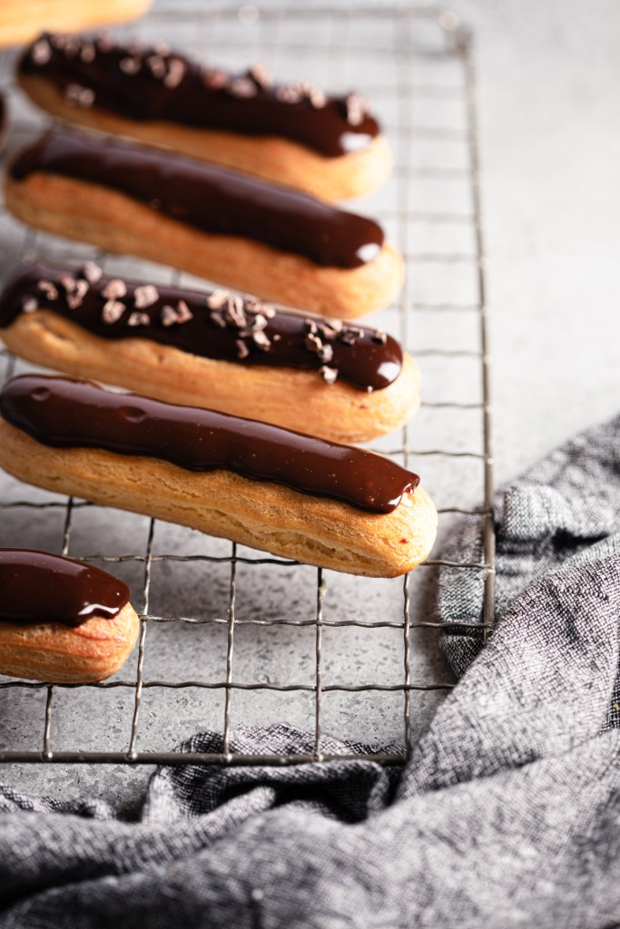 eclairs in a line with ganache and cocoa nibs