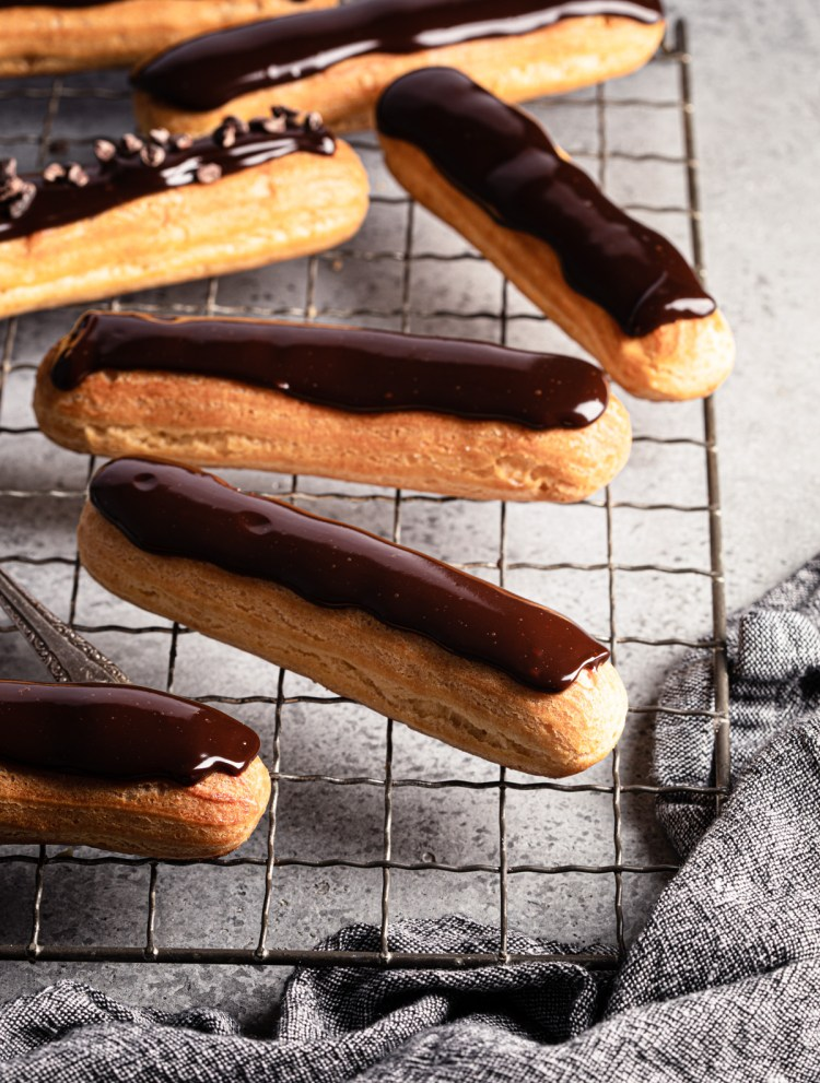 french eclairs scattered on a crinkle cooling rack