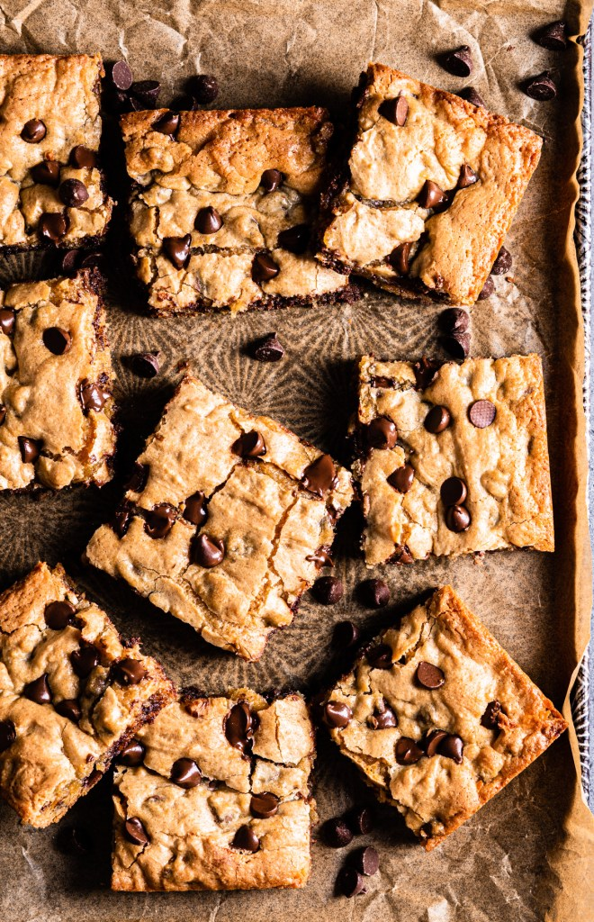 chocolate chip blondies on brown parchment paper with a baking pan underneath