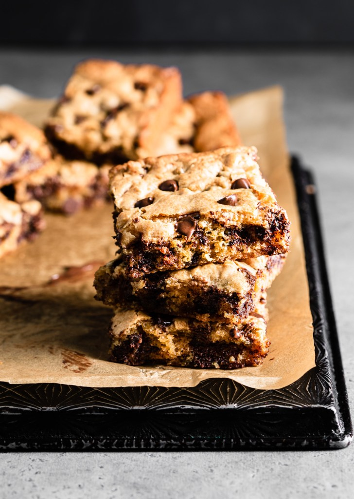 stack of chocolate chip blondies on a baking tray with parchment paper