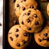 Soft pumpkin chocolate chip cookies (bakery style) on a dark baking tray
