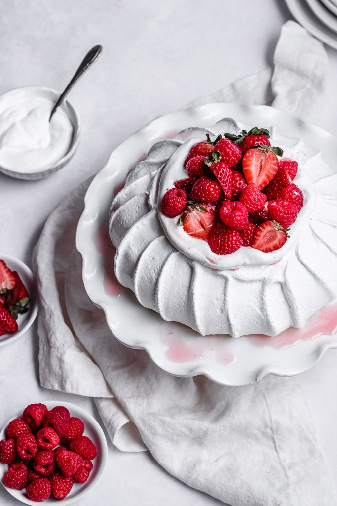 easy pavlova topped with berries and whipped cream