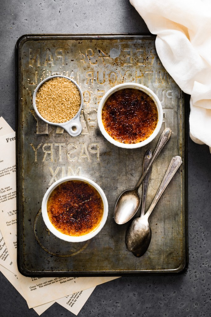 ramekins of pumpkin creme brulee and spoons on a tray