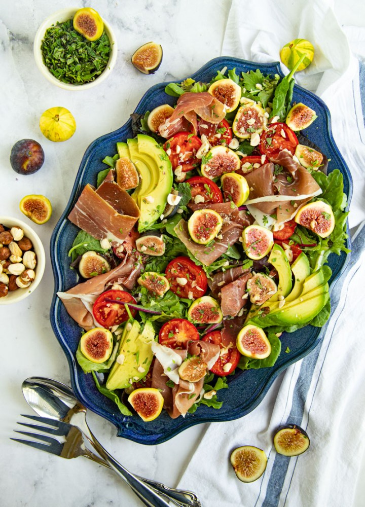 Salad with fresh figs, prosciutto, tomatoes, avocado and fresh greens on a blue platter