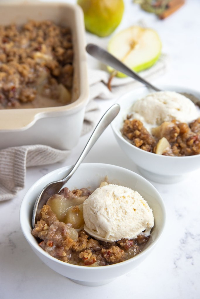 Two bowls of pear crisp topped with vanilla ice cream. The pan of pear crisp sitting the background