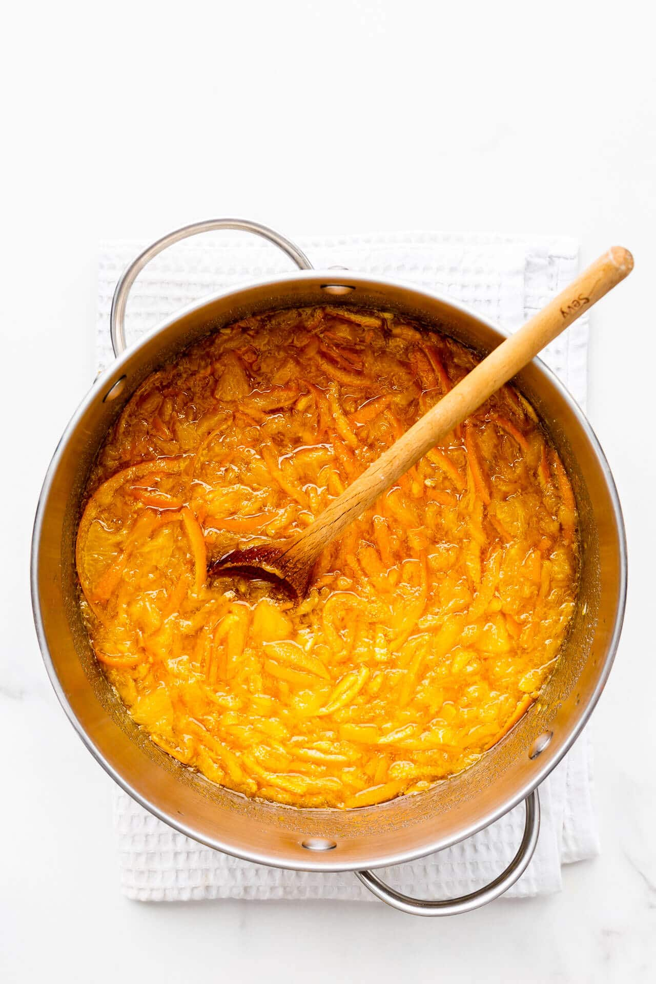 A pot of sliced oranges and sugar, ready to be boiled to make homemade orange marmalade.