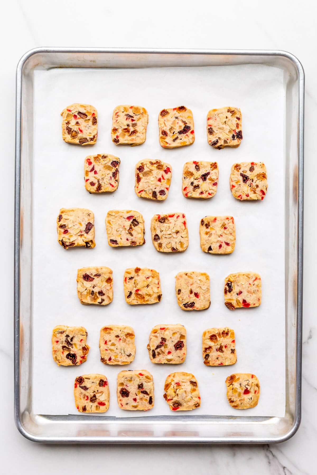 Freshly baked fruitcake cookies on a parchment-lined sheet pan.