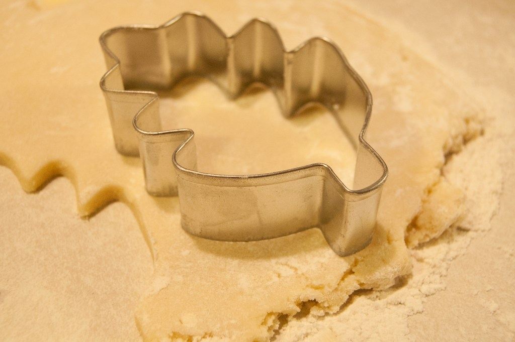 Leaf shaped cookie cutter on rolled out sheet of dough