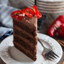 Four layers of moist, rich, and decadent Chocolate Cake, filled and frosted with a fluffy Mexican Spiced Chocolate Whipped Ganache frosting, and garnished with sweet/hot Candied Serrano Peppers. It will warm you from the inside out!