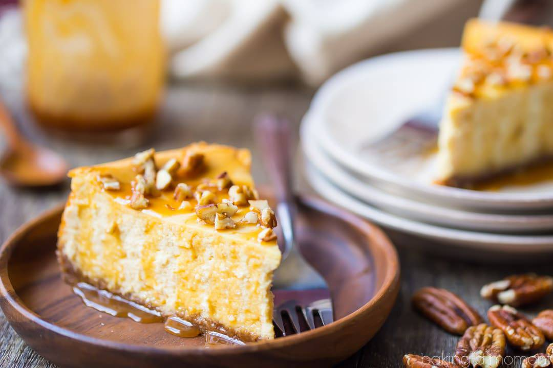 Caramel pecan cheesecake slice on a plate, garnished with caramel sauce and chopped pecans, with a stack of plates and a jar of caramel sauce in the background
