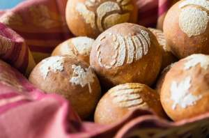 Basket lined with a red cloth, filled with bread rolls stenciled with fall/Thanksgiving themed images, on an aqua tabletop.