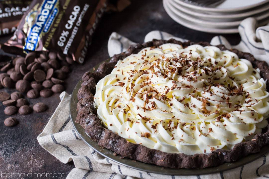 Chocolate cream pie with chocolate crust, whipped cream, and chocolate shavings on a striped cloth, with chocolate chips spilling out of the bag in the background.