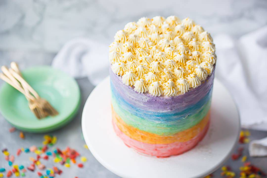 Rainbow fruity pebble cake with gold sprinkles on a cake stand with green plates, fruity pebbles cereal, and gold forks on a light gray background.