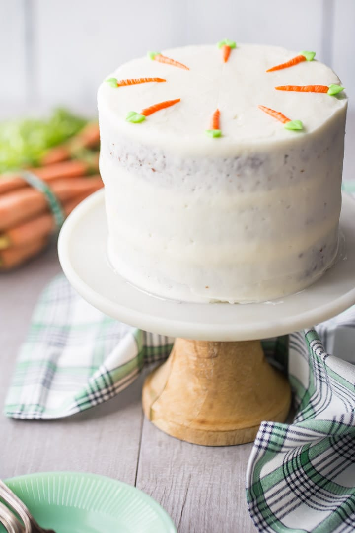Triple-layer semi-naked style carrot cake with cream cheese frosting, on a cake stand with a green plaid cloth and fresh carrots in the background.