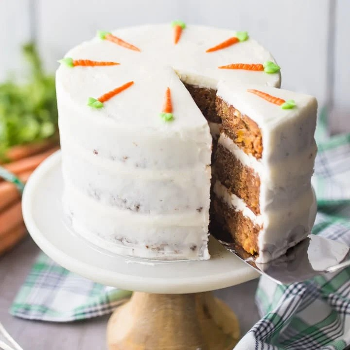 Cake server removing a slice of triple-layer carrot cake with cream cheese frosting, with a green plaid cloth below and fresh carrots in the background.